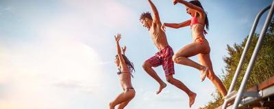 Junge Leute springen in einen See