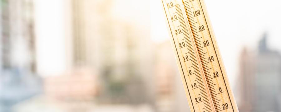 Thermometer vor Großstadt-Hintergrund