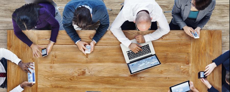 Menschen mit Laptops und Tablets sitzen an einem Tisch