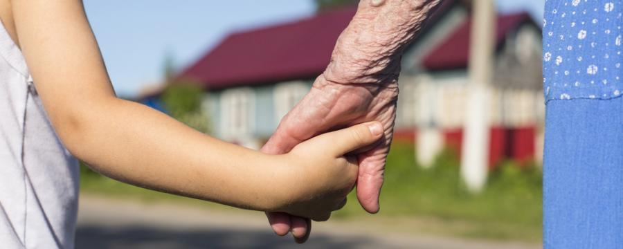 Kind und alte Frau geben einander die Hände