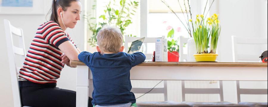 Mutter passt auf Sohn auf und arbeitet im Home-Office
