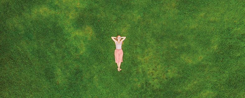 Frau liegt auf einer Wiese