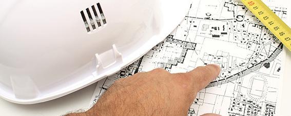 Hand deutetet auf einen Bauplan