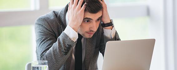 Mann verzweifelt vor Laptop
