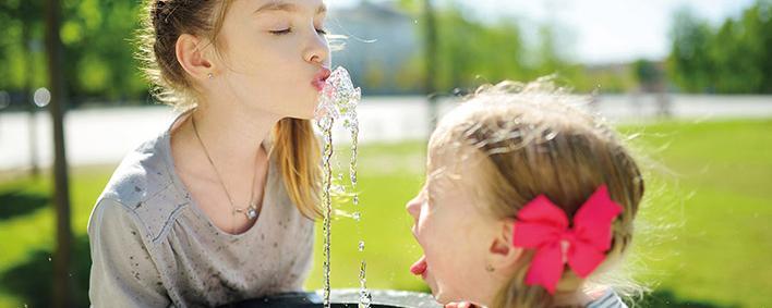 2 Mädchen bei einem Trinkwasserbrunnen