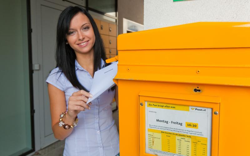 Frau mit Briefwahlkarte