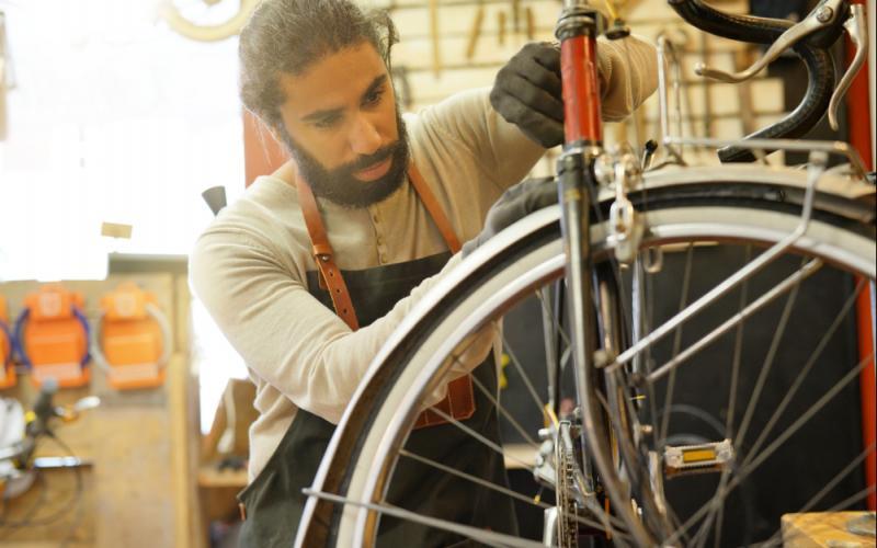 Mann repariert ein Fahrrad - Beispiel Suffizienz