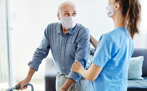 Pflegerin hilft Mann mit Rollator