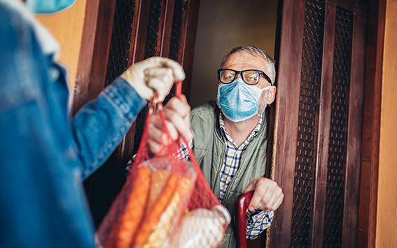 Frau bringt altem Mann während Corona Einkäufe