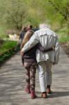 Ein junges Mädchen läuft Arm in Arm mit einem älteren Herren durch einen Park. Die Beiden sind von hinten zu sehen.