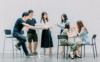 Sechs junge Menschen stehen und sitzen vor einem neutralen Hintergrund. Die beiden Personen links beschäftigen sich mit einem Tablet. Die Personen in der Mitte scheinen gemeinsam zu Lernen. Die Person am rechten Bildrand trägt einer ihr gegenübersitzenden Person Make-up auf.