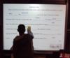Eine Person füllt einen Lückentext auf einem Whiteboard aus.