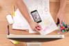 Blick aus der Vogelperspektive auf einen Schreibtisch. Eine Person überarbeitet ihre Notizen. Auf dem Tisch liegen Büroutensilien und Geräte die zur digitalen Bildung genutzt werden können.