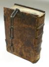 Ein altes Buch mit Ledereinband ist zu sehen, das Buch kann mithilfe einer Eisenkette verschlossen werden, ein sogenanntes Kettenbuch.