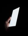 Eine Hand hält ein Smartphone mit hellem Display vor einem schwarzen Hintergrund.
