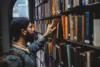 Eine Person steht vor einem Bücherregal und sucht ein Buch.
