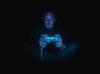 Eine Person hält einen Spielekonsolen-Controller. Sie wird frontal von einem Bildschirm beleuchtet und erscheint dadurch blau getüncht. Der Hintergrund ist tiefschwarz.