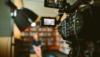 Eine Kamera filmt eine Person, die im Hintergrund nur verschwommen zu erkennen ist. Sie sitzt vor einem Bücherregal.