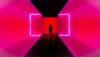 Eine Person ist von hinten zu sehen. Sie steht in einem Gang dessen Wände grell pink leuchten.
