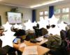 Eine Klasse sieht sich Inhalte zum Thema Nationalsozialismus an. Die Gesichter der Kinder sind aus Datenschutzgründen von weißen Sternformen überlagert.