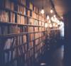 Blick entlang eines Bücherregals das in das Licht vieler Glühbirnen getaucht ist, die von der Decke hängen