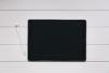 Tablet das auf einer Holzoberfläche liegt. Das Display ist ausgeschaltet, daneben liegt ein Stift mit dem das Tablet bedient werden kann.