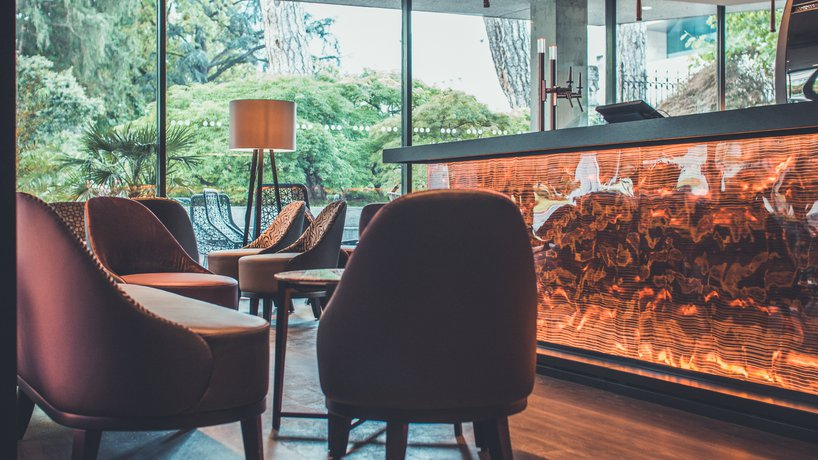 Il nostro bar, progettato dal noto architetto Gunther Thoeny, riunisce, in un ambiente funzionale, elementi di design, una calda illuminazione artificiale e ampie vetrate sul parco