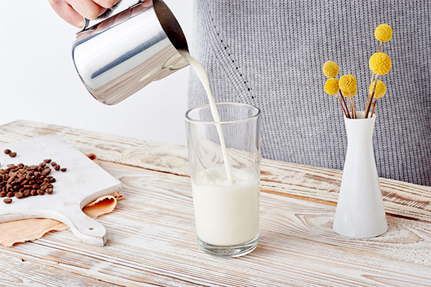 Milch wird in Latte Macchiato Glas gegeben