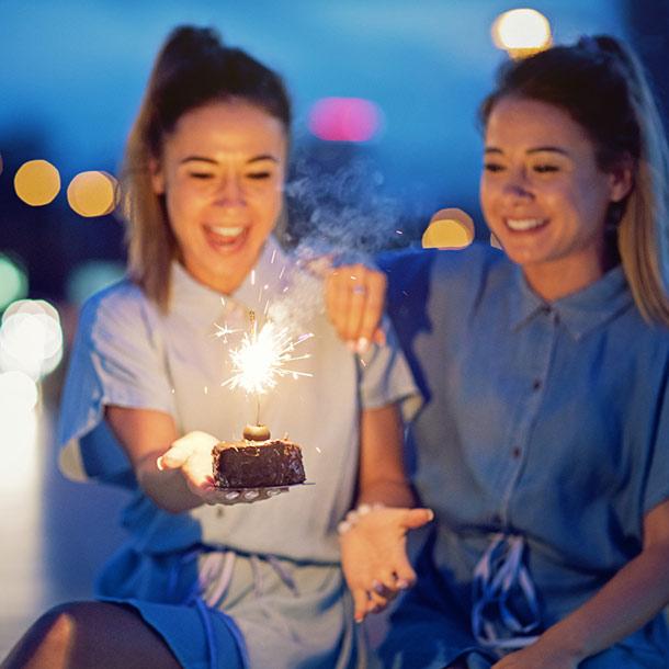 Mädchen feiern Geburtstag mit Kuchen und Wunderkerze
