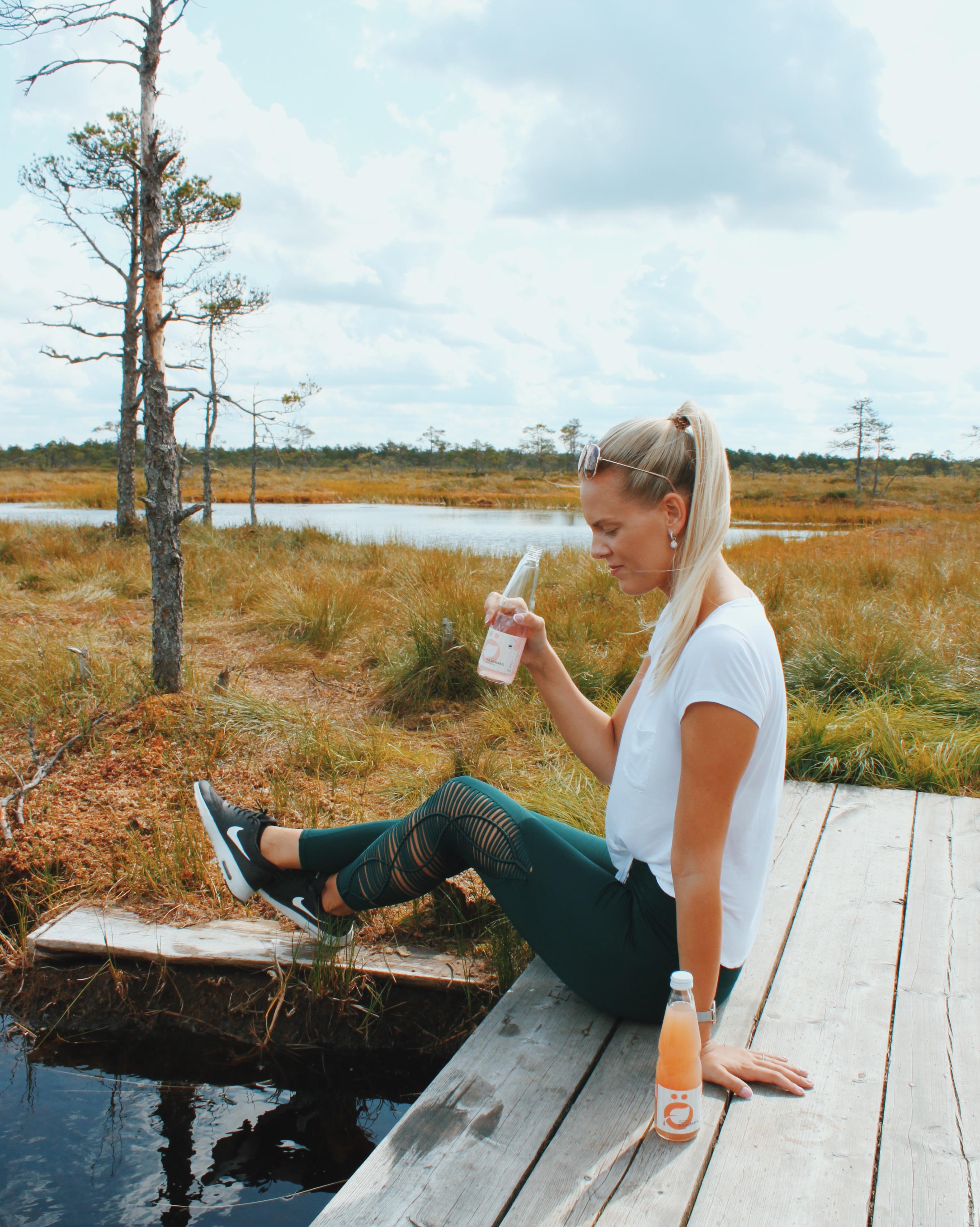 Blonde Frau sitzt auf dem Steg und trinkt ÖselBirch Birkendrinks