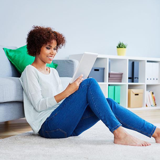 Frau sitzt auf Boden mit Tablet