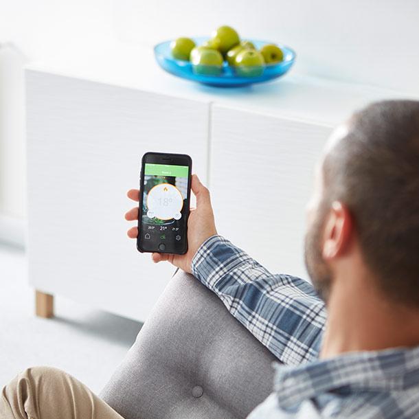 Mann benutzt App für Smart Heating System Eberle