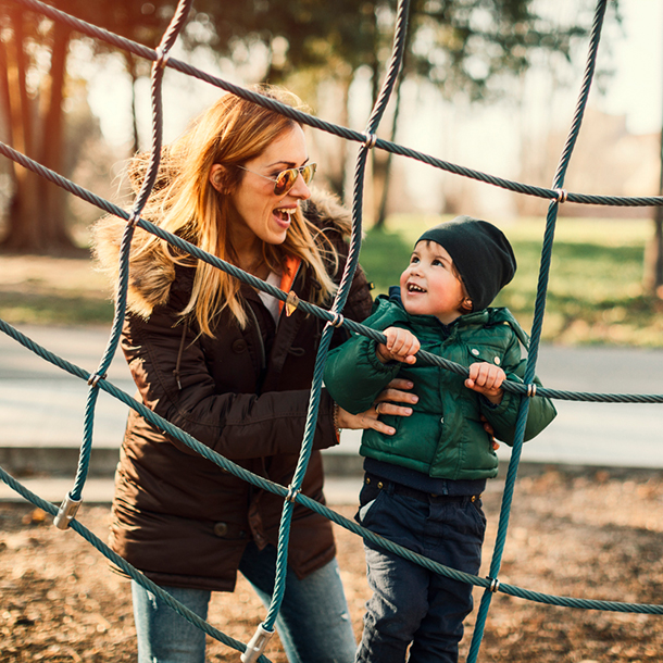 Frau mit Kind auf Spielplatz