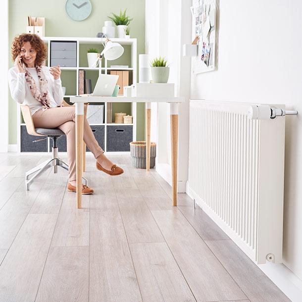 Frau sitzt mit Heizung und Wiser System zu Hause
