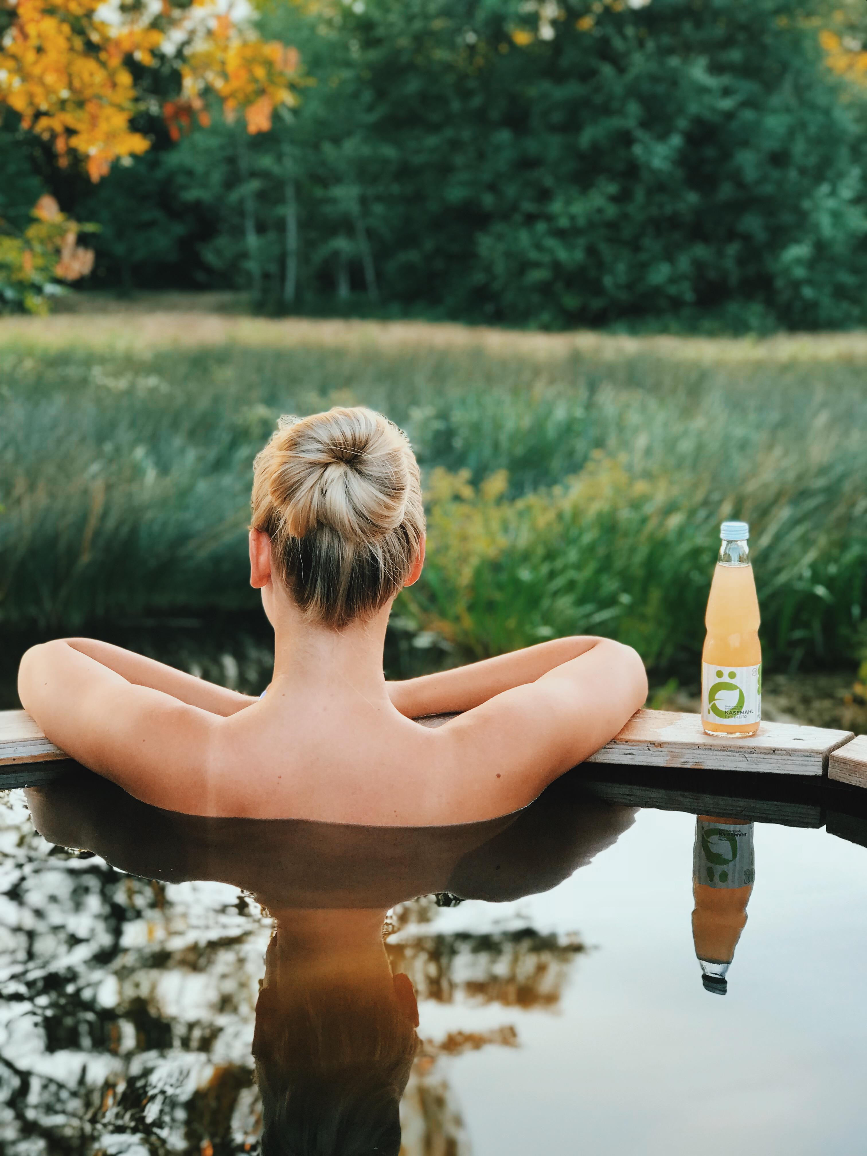 Blonde Frau trinkt ÖselBirch Birkendrinks in der Natur