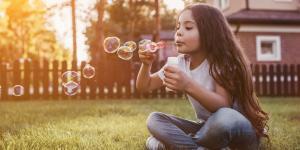 Kind sitzt auf Wiese vor Haus