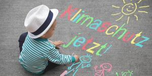 Kind sitzt auf der Straße mit Graffiti
