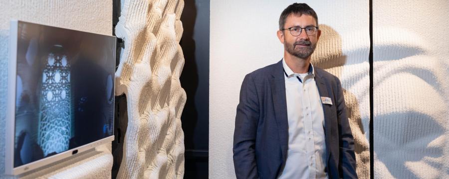 Mann vor einer gedruckten Betonskulptur