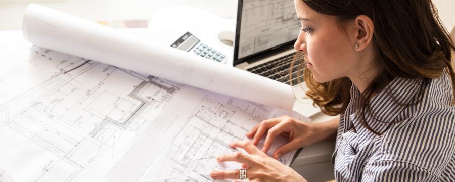 Junge Architektin über Bauplänen