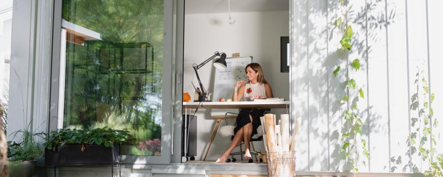Frau sitzt im Home office im Container