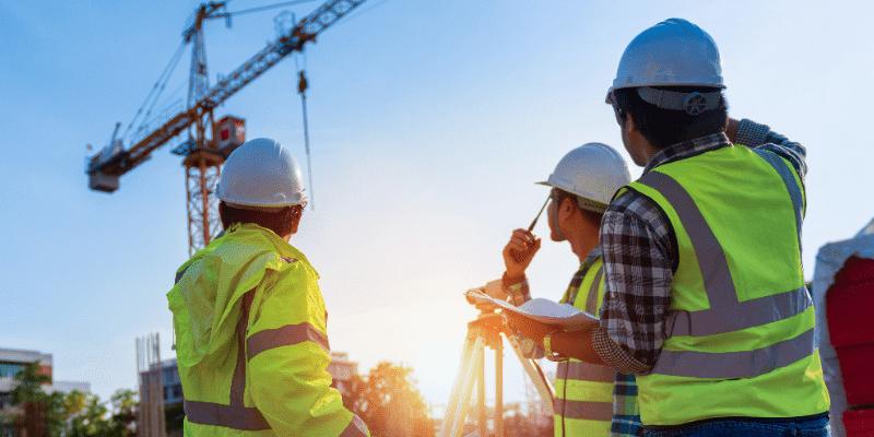 Bauarbeiter blicken auf einen Baukran
