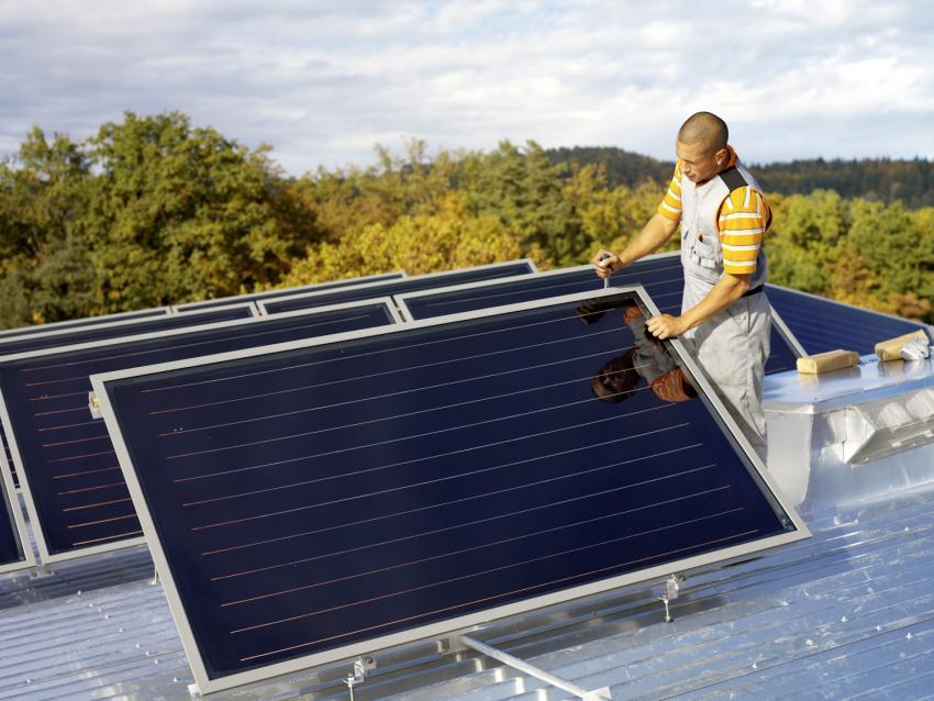 Mann neben einem Solarpanel