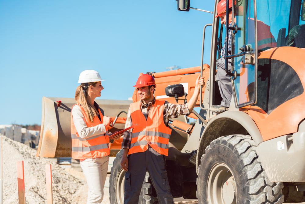 Ziviltechnikerin und Bauarbeiter auf einer Baustelle.