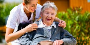 Pflegerin mit Frau im Rollstuhl