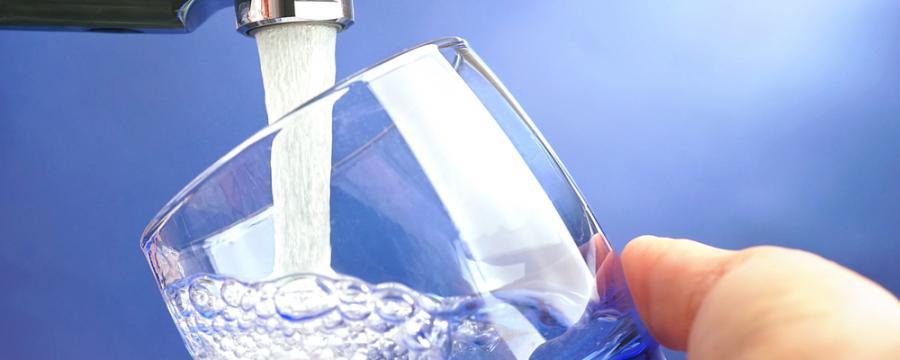 Glas wird mit Wasser aus der Leitung befüllt