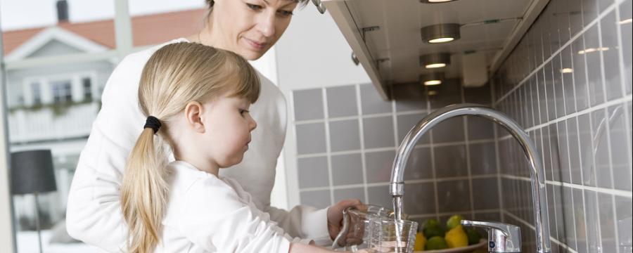 Mutter und Tochter trinken von der Wasserleitung