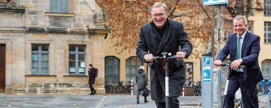 Oberbürgermeister Andreas Starke fährt mit dem E-Scooter durch Bamberg.