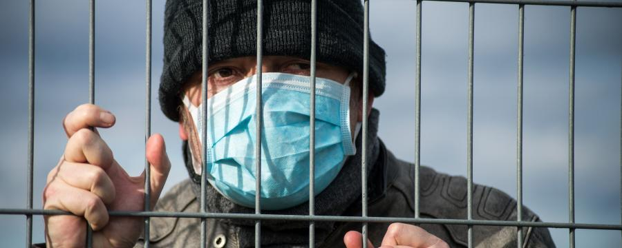 Ein Mann mit Maske hinter einem Zaun.
