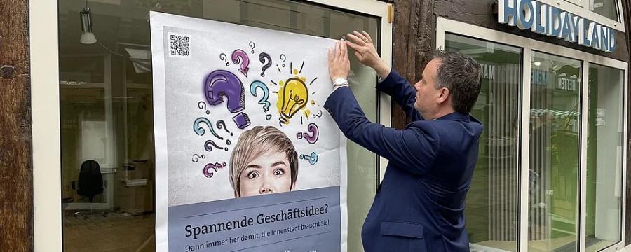 Bürgermeister von Hameln bringt Werbeplakat für Aktion Hameln Handelt an