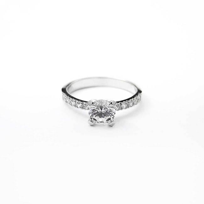 klasičen zaročni prstan z osrednjim kamnom in ob strani belo zlato